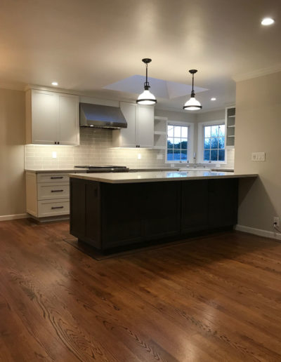 black and white kitchen with wood flooring