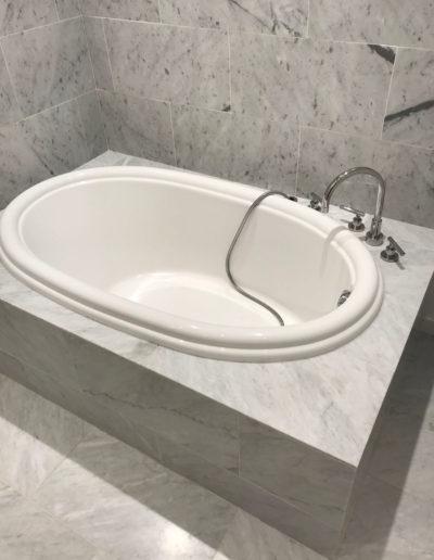 white bathtub with grey tile